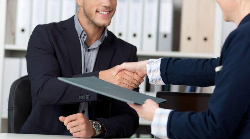 deux personnes assises en face l'une de l'autre autour d'un bureau se serrent la main